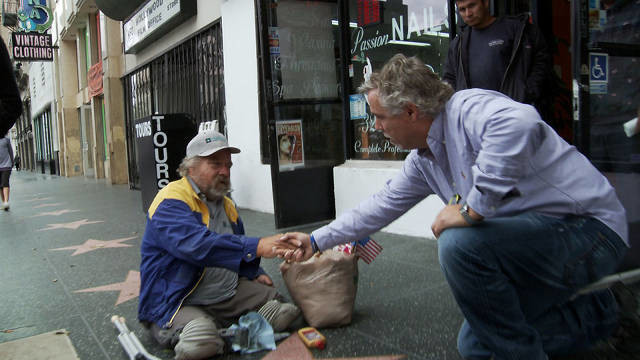 a man gives foods to a disabled and homeless person